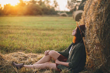 Beautiful stylish woman in hat enjoying sunset, sitting at haystacks in evening summer field. Atmospheric tranquil moment in countryside. Young fashionable female relaxing at hay bale in sunshine 版權商用圖片