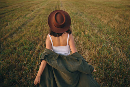 Beautiful carefree woman in hat walking in evening summer field. Happiness. Young happy stylish female relaxing in countryside, dancing and enjoying evening. Atmospheric moment. Back view