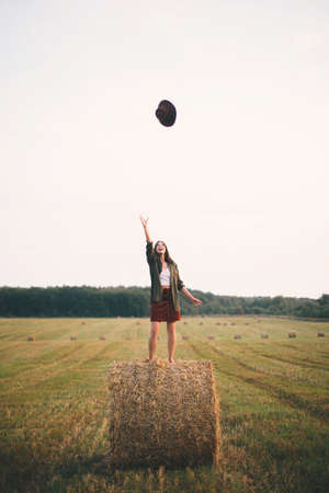 Beautiful carefree woman throw up hat in the sky while standing on haystack in evening summer field. Happiness. Young happy female  having fun on hay bales in countryside. Atmospheric moment