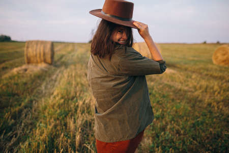 Beautiful carefree woman in hat walking and smiling in evening summer field. Young happy stylish female relaxing in countryside, enjoying evening. Atmospheric moment.