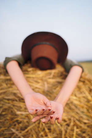 Beautiful carefree woman in hat lying on haystack enjoying evening in summer field, hands close up. Young happy female relaxing on hay bale in countryside. Atmospheric tranquil moment