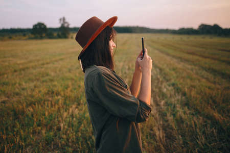 Beautiful stylish woman in hat taking photo of sunset on phone in summer field. Portrait of young attractive female holding smartphone and capturing evening in warm sunshine. Atmospheric moment 版權商用圖片