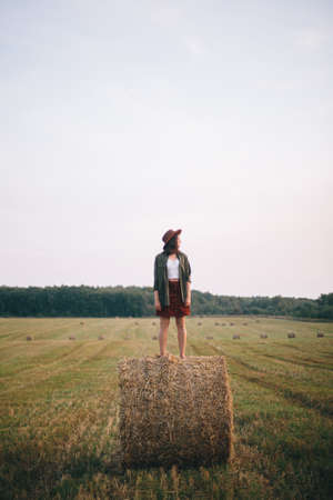 Beautiful carefree woman in hat standing on haystack enjoying evening in summer field. Young happy female relaxing on hay bale in countryside. Atmospheric tranquil moment