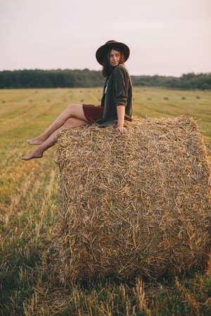 Beautiful happy woman sitting on haystack in sunset light in evening summer field. Young happy female relaxing on hay bale in countryside. Atmospheric tranquil moment