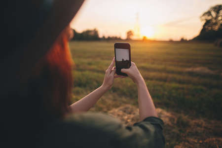 Stylish woman taking photo of sunset on phone in summer field. Young female holding smartphone and capturing evening warm sunshine in countryside. Atmospheric beautiful moment 版權商用圖片