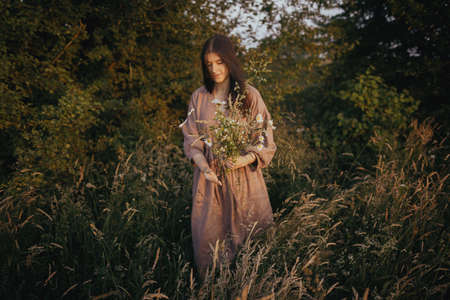 Beautiful woman in linen dress gathering wildflowers in summer meadow in sunny evening. Atmospheric rural moment. Stylish young female in rustic dress picking flowers in countryside. Slow life Reklamní fotografie