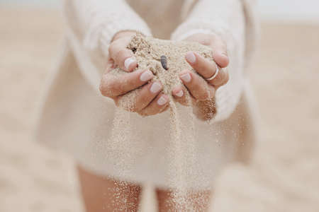 Hands holding sand on background of beach, carefree moment. Stylish young woman in sweater releasing sand on coast. Sand running through hands. Time concept. Summer beach and vacation