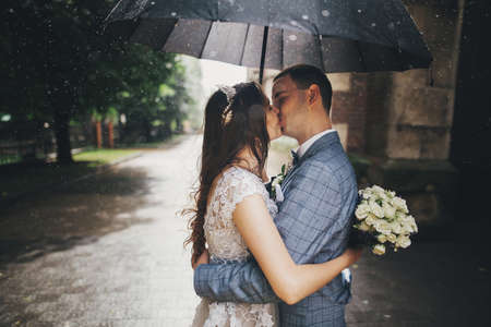 Stylish bride with bouquet and groom kissing under umbrella on background of old church in rain. Provence wedding. Beautiful wedding couple embracing under black umbrella in rainy street
