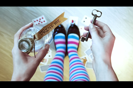 lewis carroll: Alice in wonderland. Background. A key and a potion in hands against a floor