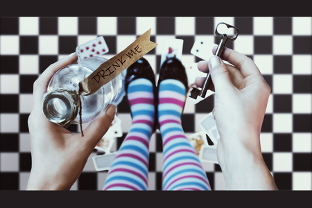 lewis carroll: Alice in wonderland. Background. A key and a potion in hands against a chess floor