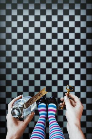 Alice in Wonderland. Achtergrond. Een sleutel en een drankje in handen tegen een schaakspel vloer
