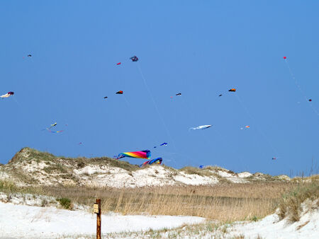 yachtsman: flying kite in the wind over the dunes along the North Sea