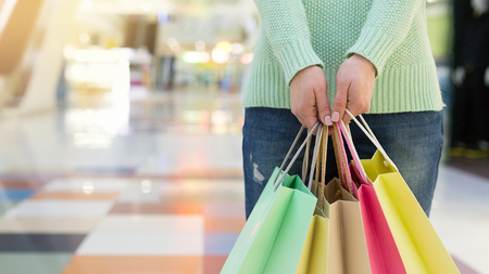 Young woman holding colorful shopping bags in shopping mall