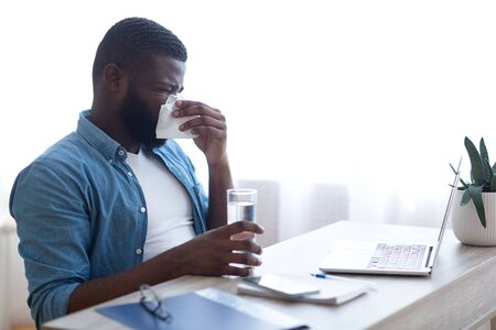 Portrait of sick man blowing his nose with a tissue paper and holding a glass of water at workplace.