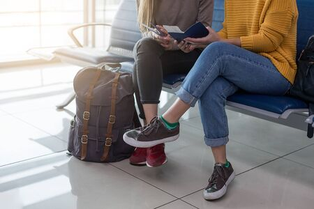 Two women sitting in airport waiting zone, discussing their trip and checking flight details.