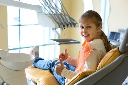 Small girl with a cute smile sitting on a dentist chair covering with a napkin waiting for a doctor Stok Fotoğraf