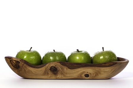 Line of four newly-washed organic green apples in a narrow carved olive wood bowl