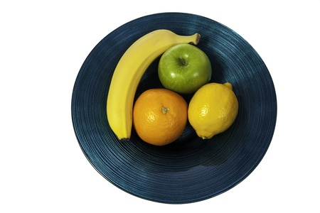 A colorful selection of fresh fruit in a modern blue glass bowl  The lemon, orange, apple and banana stand out beautifully against the bowl and signify health and modernity  Stock Photo