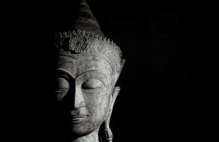 Moody high contrast image of a beautiful buddha head against a black background  The face is serene and showing peaceful meditative contemplation  Stock Photo