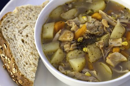 Homemade chicken soup  one of the simplest and healthiest of all homemade foods  This is a bowl of chunky chicken soup, seasoned with mixed herbs and served with brown oatmeal bread