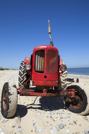 This quirky and slightly dilapidated red beach tractor was caught on a bright summer