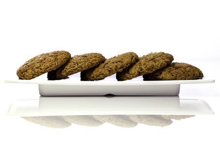 Homemade traditional and sugar-rich ginger cookies laid out on a serving plate  Image is isolated against a white background and shown with reflection