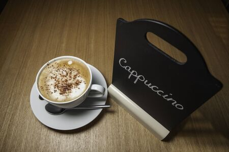 Feshly brewed morning cappuccino shown on cafe table with blackboard menu  Stock Photo