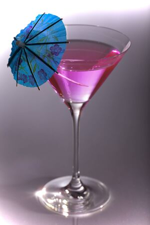 Pink party cocktail with contrasting blue umbrella   Stock Photo