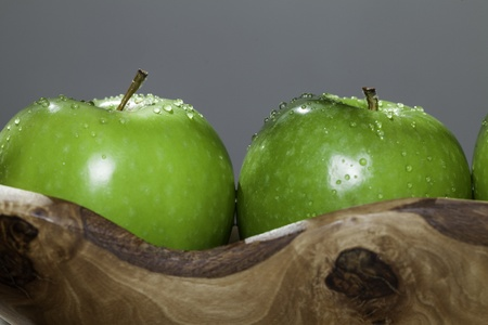 Two freshly washed organic apples isolated against a plain grey background