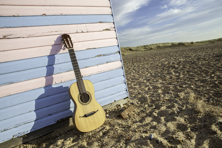 Parlour-sized classical acoustic guitar resting against a beach hut painted in pastel pink and blue. Symbolic of vacation and beach fun. Exaggerated angle shows the guitar; beach hut; sand and blue sky Stock Photo