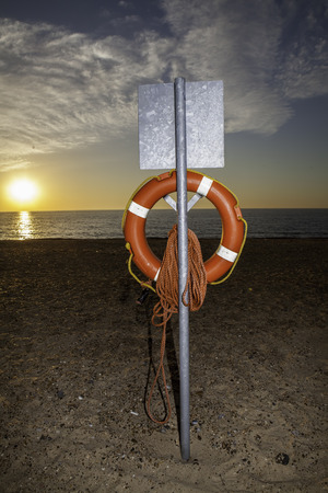 Clear view of a lifesaver buoyancy aid at sunrise. As the day begins it is poignant that the beach will fill and the aid could be called for.