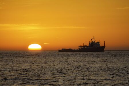 Fishing vessel trawling off the East Coast of the UK at sunrise. The trawler is shown in silhouette against a natural vivid orange sky as the sun rises from the surface of the water. Stock Photo