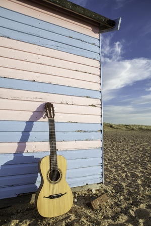 Parlour-sized classical acoustic guitar resting against a beach hut painted in pastel pink and blue. Symbolic of vacation; relaxation and beach fun.