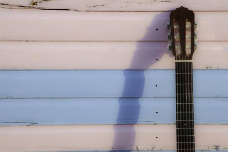 Classical guitar neck with shadow on the boards of a pastel pink and blue beach hut. Neck to the side to allow copy space. The image reflects the notion of a summer vacation - relaxation; beaches;  casual music; and fun.