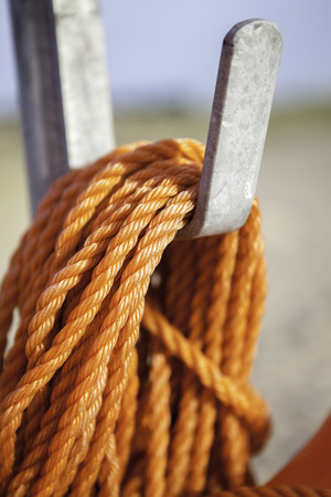 coiled rope: Orange nylon rope coiled around a metal hook. Focus is on rope at foreground. Stock Photo