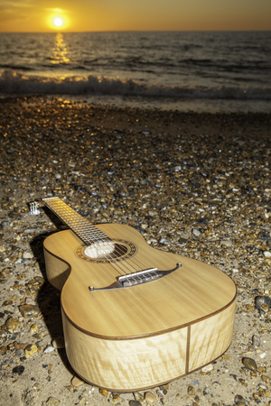 aftermath: A classical parlour sized acoustic guitar laying on the shore at sunrise or sunset. The image is symbollic of vacation and the aftermath of a beach party Stock Photo