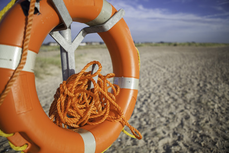 Beach lifesaver with dangerously tangled rope. Time would have to be taken to untangle the rope before it could be used.