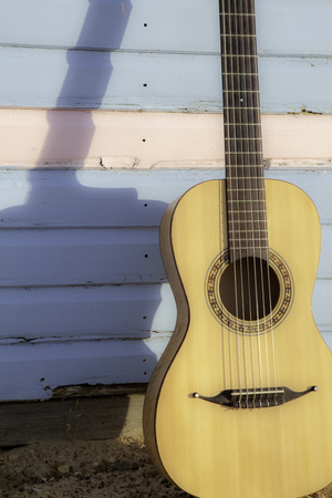 Parlour-sized classical acoustic guitar resting against a beach hut painted in pastel pink and blue. Symbolic of vacation and beach relaxation. Stock Photo