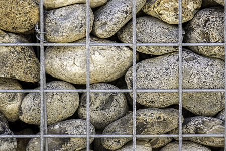 large rocks: Large rocks supported by a cage. An abstract texture background with many connotations. Stock Photo
