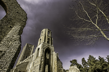 This is a picture of the partly ruined Wymondham Abbey, a magnificent Norman church in Norfolk UK. It was established in 1107. The tone emphasises the dramatic nature of the building as does the perspective which also allows some central copy space. Stock Photo
