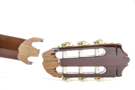 snapped: Headstock of a classical guitar that has snapped off and is awaiting repair. Isolated against a white background.