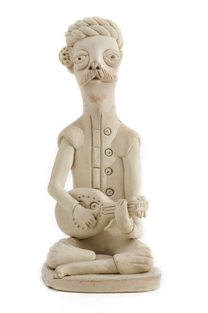 Pottery figure of Indian musician with legs crossed playing a stringed instrument. Stock Photo