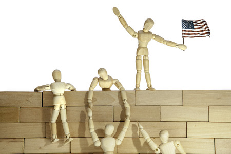 usa flags: People climbing a USA border wall. Connotations of teamwork, illegal immigration and success. Stock Photo