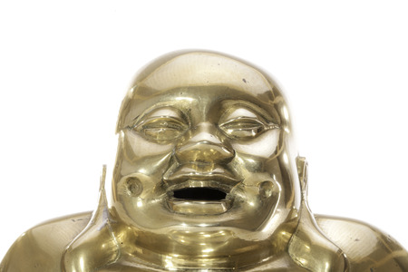 Happy laughing face of a traditional brass buddha. Glowing and in close up against a white background.