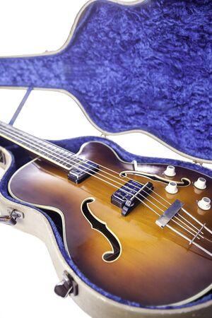 humbucker: A vintage semi-acoustic archtop bass guitar with sunburst finish in original tweed case. Stock Photo