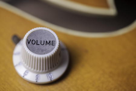 loudness: Close up of a retro volume control on a vintage guitar.
