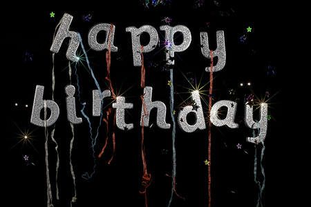 party poppers: Happy Birthday. Happy birthday in silver glitter party text with streamers stars and fireworks effect. Ideal birthday card, party invitation or poster image.