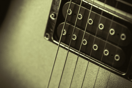 transducer: Black humbucker pickup on a gold guitar. Retro monochrome image with a soft feel. Nice background or poster image for a rock, blues, or jazz music club, with copy space.