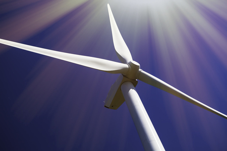 Solar and wind power. Turbine in bright sunshine. Close up of wind turbine rotor and blades in the bright sun and contrasting with plain blue sky. Stockfoto