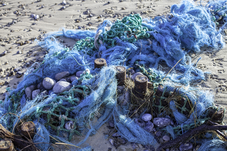 concern: Blue tangled fishing nets washed up on the shore. An environmental issue as the nets are a dangerous form of plastic pollution providing a hazard to ocean wildlife.